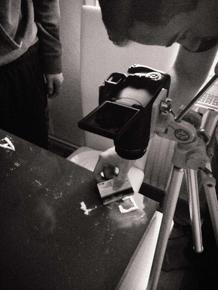 HaulyShit legt gerade Buchstaben aus Mehl und fotografiert sie für die weitere Darstellung des Covers